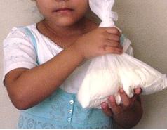 Una niña cubana muestra la cantidad de leche en polvo que le venden por el racionamiento del mes