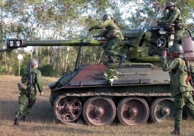 """HAB05 - LA HABANA (CUBA), 16/12/04.- Varios soldados cubanos maniobran junto a un vehículo blindado en una operación de """"desplazamiento de la técnica en el terreno"""" efectuada al este de La Habana (Cuba) hoy, jueves 16 de diciembre, como parte del ejercicio estratégico Bastión 2004 que se celebra en toda Cuba hasta el próximo día 19. Días antes de comenzar las maniobras, el General de Ejercito Raúl Castro, Ministro de las Fuerzas Armadas y hermano del presidente Fidel Castro comentó: """"para nosotros, evitar la guerra equivale a ganarla. Pero para ganarla evitándola, hay que derramar ríos de sudor, que es preferible a ríos de sangre"""". EFE/Randy Rodríguez/AIN"""