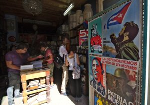 HAB100. LA HABANA (CUBA), 05/12/2016.- Varias personas revisan libros usados junto a carteles políticos hoy, 5 de diciembre de 2016, un día después de la inhumación de las cenizas del líder cubano Fidel Castro. La capital del país regresa a su vida cotidiana, tras nueve días de duelo nacional por la muerte de Castro. EFE/Rolando Pujol